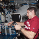 Astronaut Mike Hopkins operating one of the GAPs containing the AES-1 experiment onboard ISS (Photo credit: NASA).